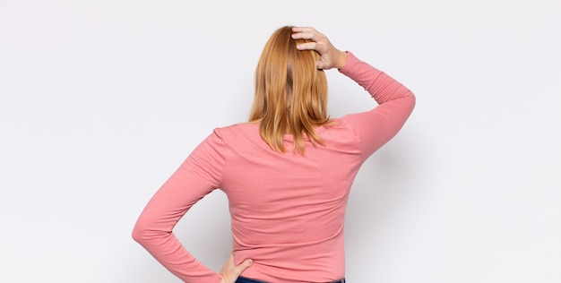 빨간 머리 예쁜 여자가 우둔하고 혼란스럽고, 엉덩이에 손을, 머리에 다른 손으로 해결책을 생각하고, 후면보기