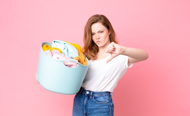 Red head pretty woman feeling cross,showing thumbs down and holding a wash basket with clothes