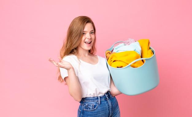 Рыжая красивая женщина чувствует себя счастливой, удивленной, осознавая решение или идею и держа корзину с одеждой