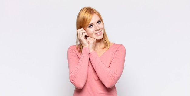 Red head pretty woman feeling in love and looking cute, adorable and happy, smiling romantically with hands next to face