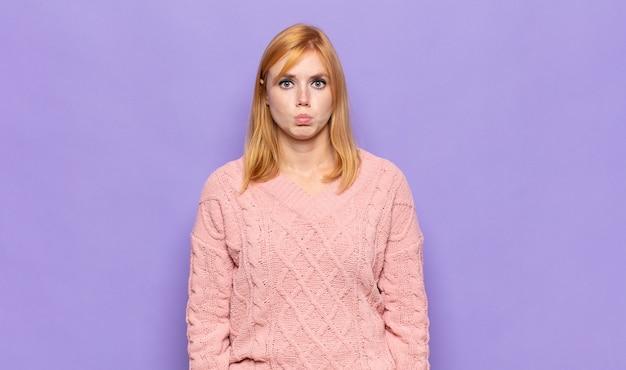 Рыжая красивая женщина грустит и испытывает стресс, расстроена из-за неприятного сюрприза, с негативным, тревожным взглядом