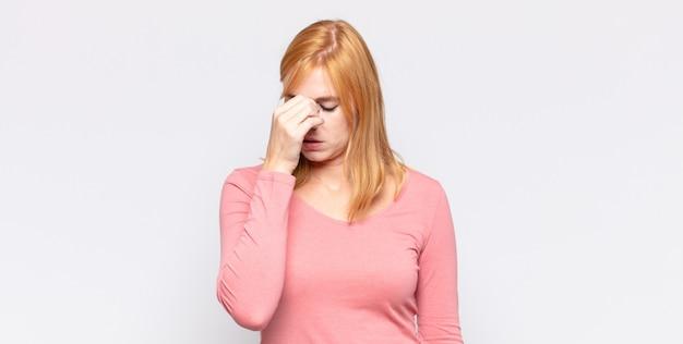 빨간 머리 예쁜 여자는 스트레스, 불행 및 좌절감을 느끼고 이마를 만지고 심한 두통의 편두통을 겪습니다.