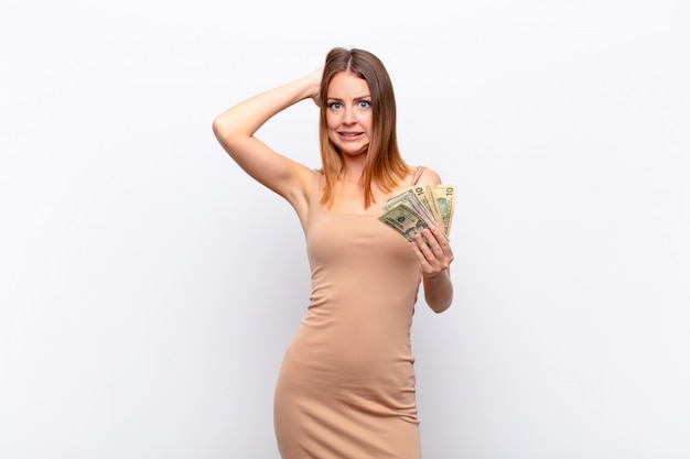 Red head pretty woman feeling stressed, worried, anxious or scared, with hands on head, panicking at mistake with dollar banknotes