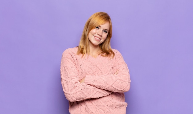 Red head pretty woman laughing happily with arms crossed, with a relaxed, positive and satisfied pose