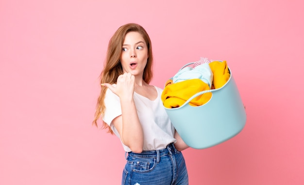 Red head pretty woman looking astonished in disbelief and holding a wash basket with clothes