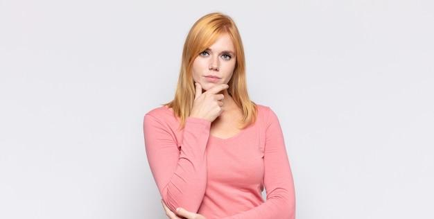 Рыжая красивая женщина выглядит серьезной, сбитой с толку, неуверенной и задумчивой, сомневающейся среди вариантов или вариантов
