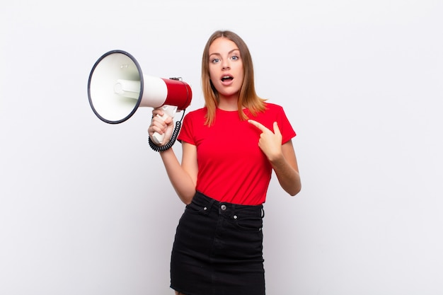 Red head pretty woman looking shocked and surprised with mouth wide open, pointing to self with a megaphone