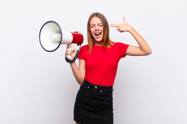 Рыжая красивая женщина выглядит несчастной и подчеркнутой, жест самоубийцы делает знак пистолет рукой, указывая на голову с мегафоном