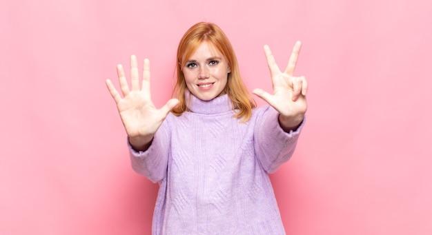 빨간 머리 예쁜 여자가 미소하고 친절하게보고, 앞으로 손으로 8 또는 8 번째를 보여주는, 카운트 다운