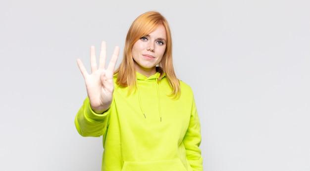 Рыжая красивая женщина улыбается и выглядит дружелюбно, показывает номер четыре или четвертый с рукой вперед, отсчитывая