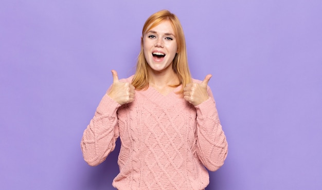 Red head pretty woman smiling broadly looking happy, positive, confident and successful, with both thumbs up