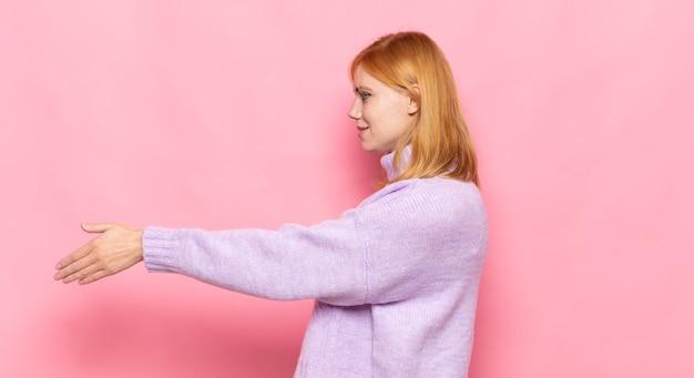 赤毛のきれいな女性が笑顔で挨拶し、握手をして成功した取引を成立させる、協力コンセプト