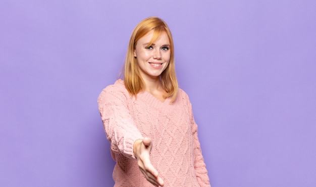 Red head pretty woman smiling, looking happy, confident and friendly, offering a handshake to close a deal, cooperating