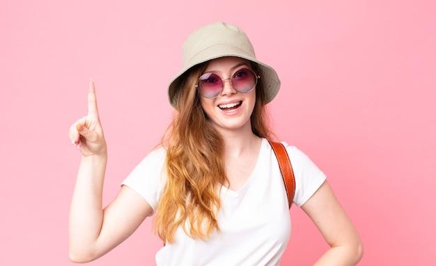 아이디어를 실현한 후 행복하고 흥분된 천재처럼 느끼는 빨간 머리 예쁜 여자 관광객