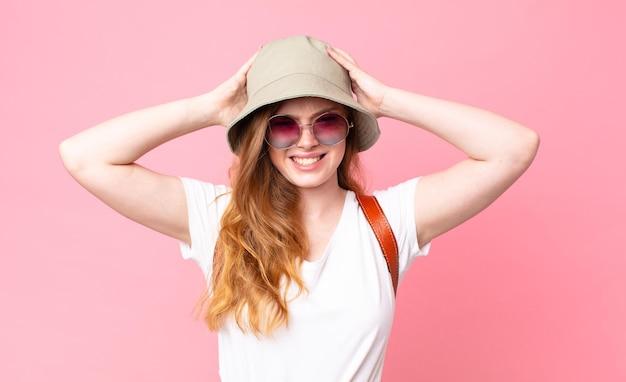 赤い頭のきれいな女性の観光客は、頭に手を置いて、ストレス、不安、または恐怖を感じています