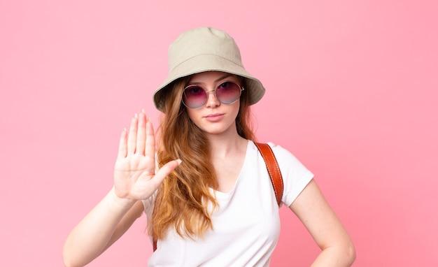 Рыжая красивая женщина-турист выглядит серьезно, показывая открытую ладонь, делая стоп-жест