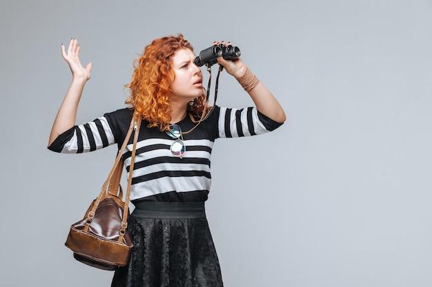 쌍안경을 통해 보이는 빨간 머리 관광 소녀