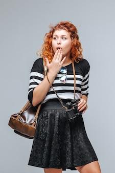 배낭에 회색 배경에 빨간 머리 관광 소녀