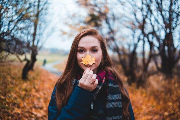 Рыжая женщина в лесу осенью