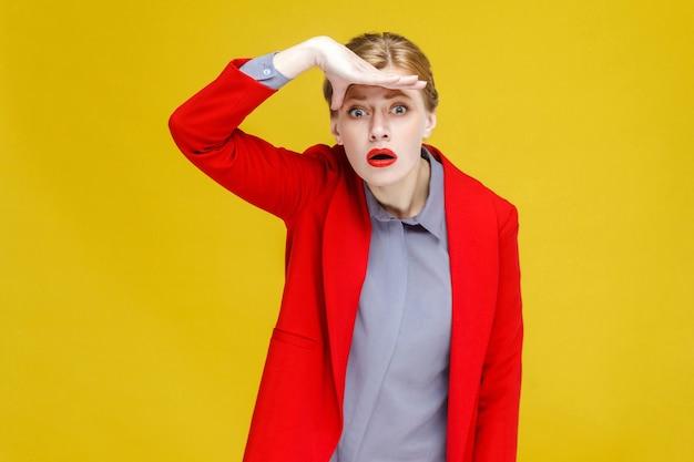 멀리 보고 빨간 양복에 빨간 머리 여자. 스튜디오 촬영, 노란색 배경에 고립