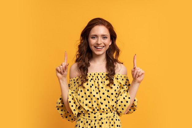 노란색에 포즈를 취하는 노란색 여름 드레스를 입고 위를 가리키는 suprice 얼굴을 가진 빨간 머리 여자