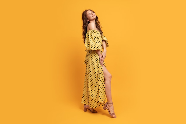 Red-head woman in yellow dress posing on yellow. summer mood