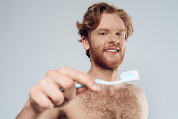 Red headed man is holding toothbrush