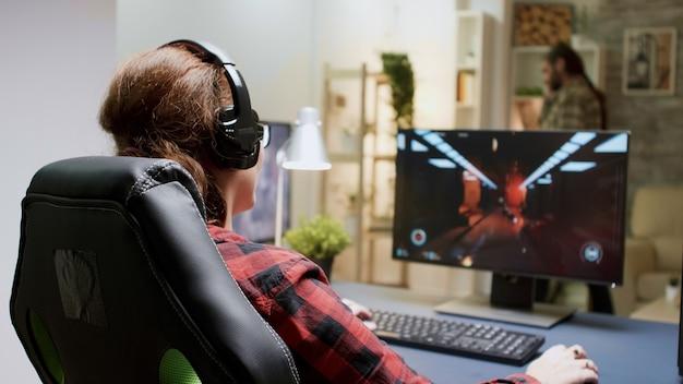 赤毛の女性は、コンピューターでシューティングゲームをプレイしているときに失ったことに腹を立てた。ゲーミングチェアに座っている女性。