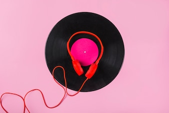 Red headphone on vinyl record over the pink background