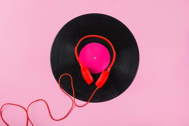 Красные наушники на виниловой пластинке на розовом фоне