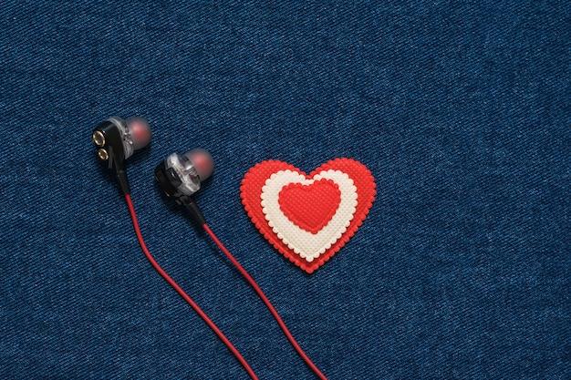 赤いヘッドフォンとデニムの背景に赤と白のハート。ファッショナブルな服のロマンチックなスタイル。