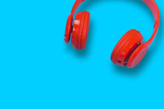 Red headphones on blue pastel table