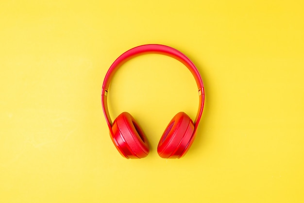 Red headphones listens to music on smartphone over yellow background.