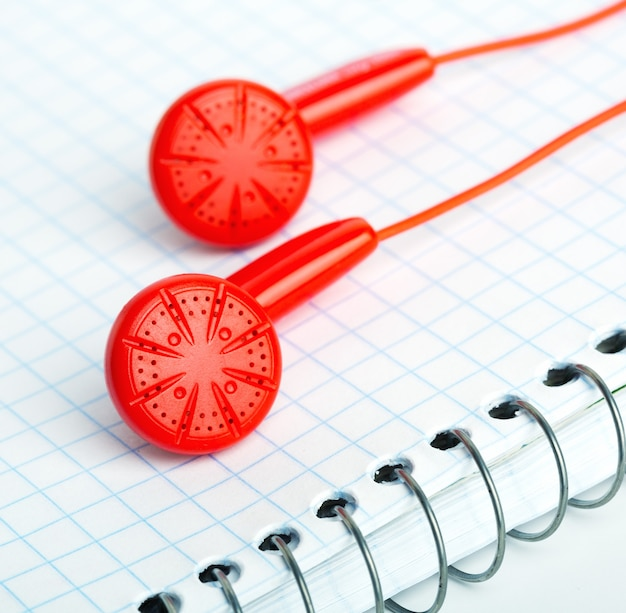 Red headphones over notebook diagonal image