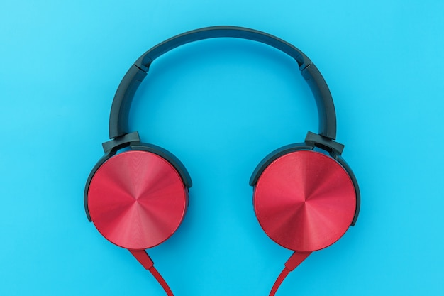 Red headphones with cable isolated on blue pastel colorful background