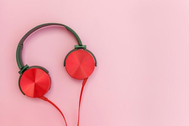 Красные наушники с кабелем, изолированные на розовом фоне пастельных красочных