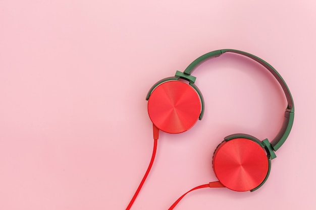 Red headphones with cable isolated on pink pastel colorful background