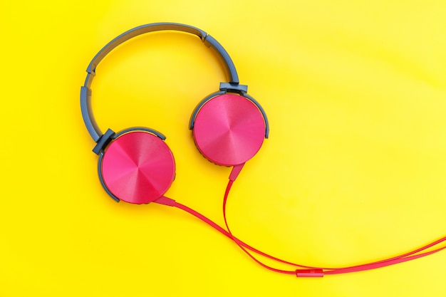 Red headphones with cable isolated on yellow colorful background