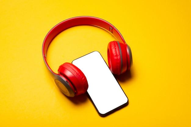黄色の真ん中に白い画面とスマートフォンと赤いヘッドフォン