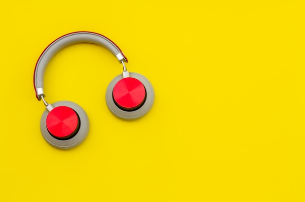 Red headphones on yellow background. music concept.