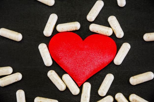 Красное сердце и капсулы на черном концепция здоровья болезни сердца
