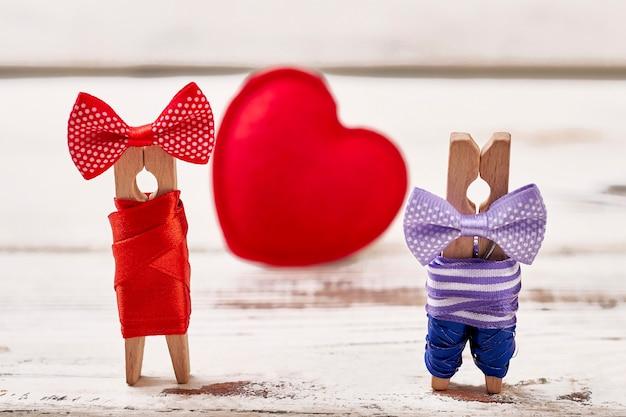 Красное сердце и пара прищепки. сердце на деревянных фоне. персонализация пары прищепками.