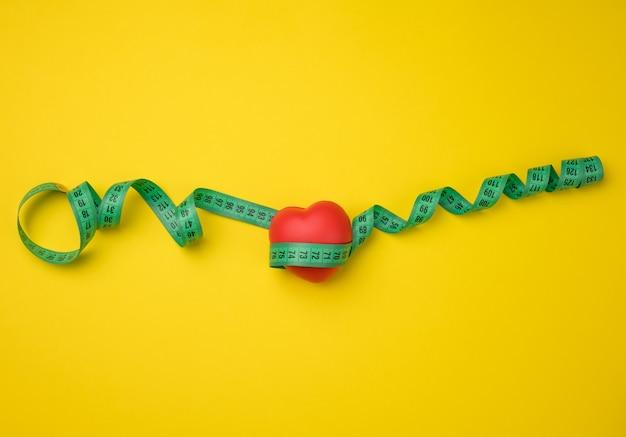 Красное сердце и зеленая измерительная лента, вид сверху