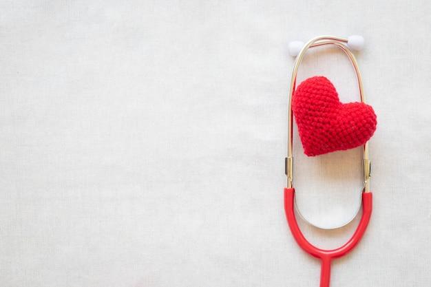 Красное сердце и стетоскоп. концепция здоровья сердца, кардиология, всемирный день сердца, гипертония.