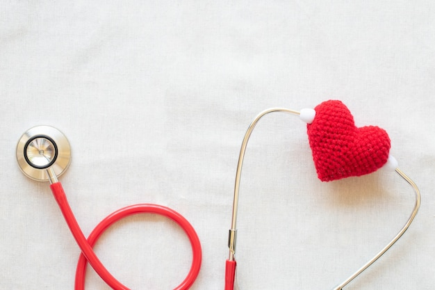 Красное сердце и стетоскоп, здоровье сердца, кардиология, день врача, всемирный день сердца, гипертония.