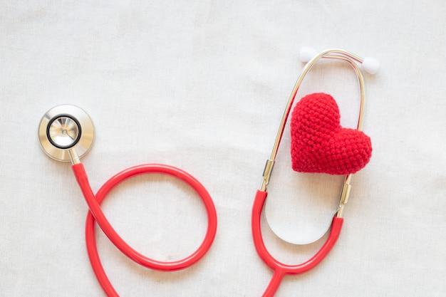 Красное сердце и стетоскоп. здоровье сердца, кардиология, страховка, донорство органов.