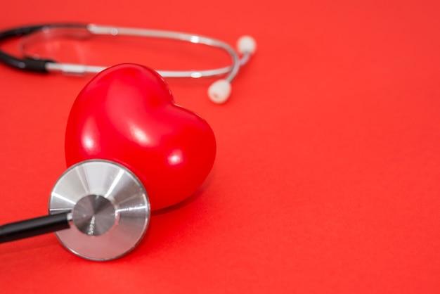 コピースペースと孤立した赤い背景に赤いハートと聴診器。健康の概念、心臓病。