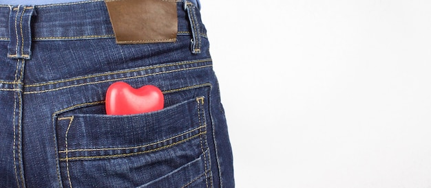 Red heart in back pocket of jeans. the concept of romance.