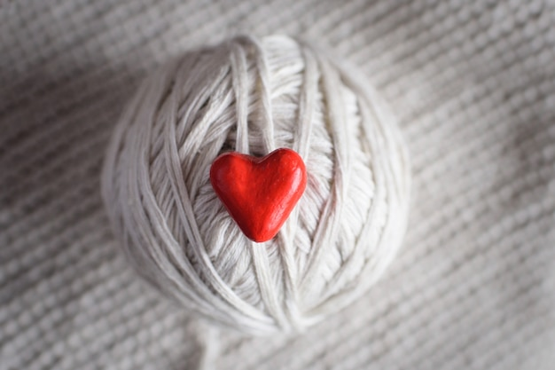 Red heart and a ball of threads on a knitted background