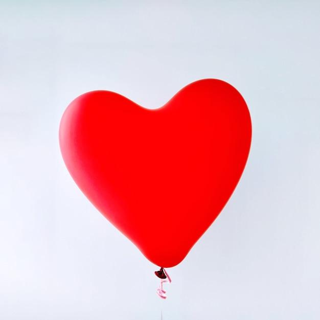 白い背景の上の赤いハートバルーンテンプレート。抽象的な愛のシンボル。幸せなバレンタインデー。パーティーや誕生日のテンプレートを祝う